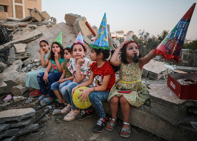 Sabih family and friends of 13 year old Mahmoud Sabih celebrate his birthday near the debris of their former house, collapsed after Israeli attacks began on May 10 in Gaza Strip, Gaza on May 25, 2021. (Photo by Mustafa Hassona/Anadolu Agency via Getty Images)