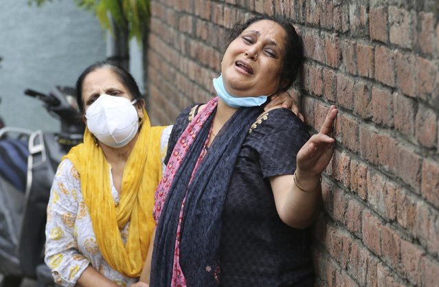 Relatives of Rakesh Pandita, a politician who was killed late Wednesday, mourns at their residence in Jammu, India, Thursday, June.3, 2021. Assailants fatally shot the politician belonging to India's ruling party in disputed Kashmir, police said Thursday, blaming separatist rebels for the attack. The unidentified assailants fired at Pandita late Wednesday in the southern town of Tral, where he was visiting a friend, police said. He was declared dead in a hospital. (Photo by Channi Anand/AP Photo)