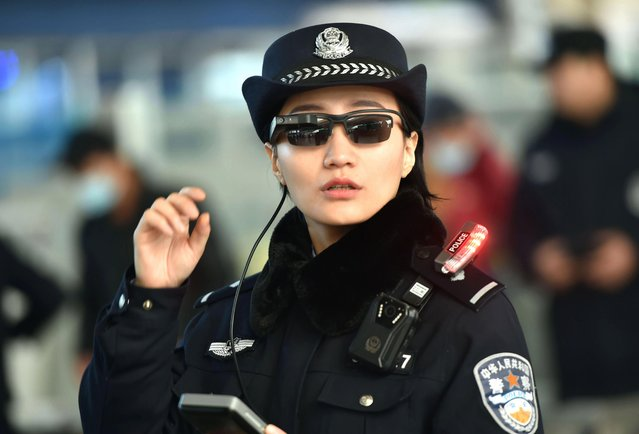 """This file picture taken on February 5, 2018 shows a police officer wearing a pair of smartglasses with a facial recognition system at Zhengzhou East Railway Station in Zhengzhou in China' s central Henan province As Xi Jinping embarks on a potential lifelong presidency, activists fear that the Chinese leader' s promise of a """"new era"""" will be bad for human rights under an increasingly digital- savy police state. (Photo by Joanna Chiu/AFP Photo)"""