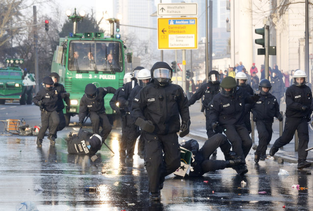 Police forces chase protestors who try to blockade the new headquarters of the ECB  Wednesday, March 18, 2015 in Frankfurt, Germany, to protest against government austerity and capitalism.  (AP Photo/Michael Probst)