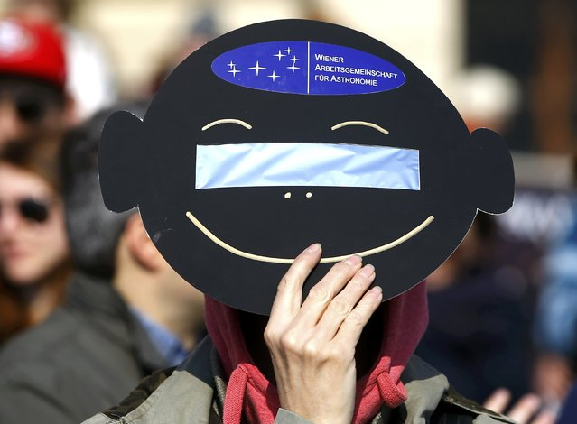 A woman uses a solar viewing filter to observe a partial solar eclipse in Vienna March 20, 2015. (Photo by Leonhard Foeger/Reuters)
