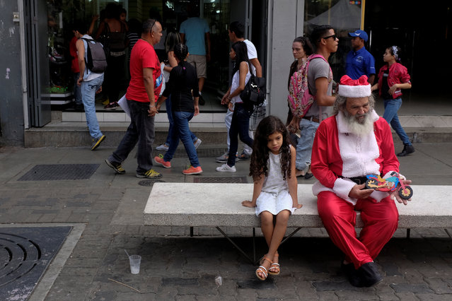A street vendor wearing a Santa Claus costume sits next to a girl at the boulevard of Sabana Grande in Caracas, Venezuela December 19, 2016. (Photo by Marco Bello/Reuters)