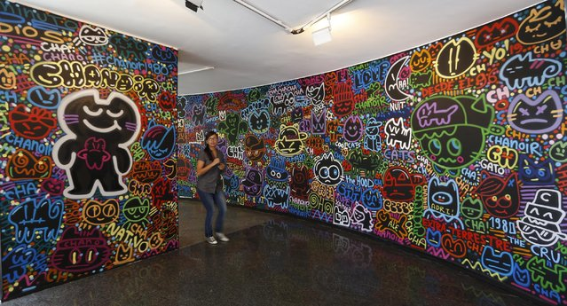 In this March 12, 2015 photo, a woman tours a graffiti exhibition at the Museum of Modern Art in Bogota, Colombia. Colombia's capital is a mecca for graffiti artists, from established artists promoted on city tours that paint murals to clandestine groups that vindicate spray painting's roots as a form of social protest roots. (Photo by Fernando Vergara/AP Photo)