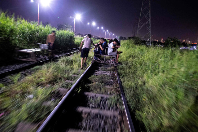 """This picture taken on October 18, 2018 shows a """"trolley boy"""" (L) pushing a home- made cart along a train track in Manila, Philippines. (Photo by Noel Celis/AFP Photo)"""