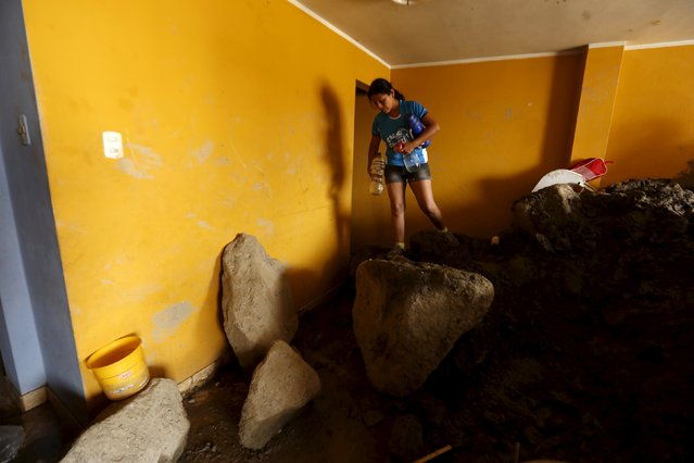 Rosa Coila walks on rocks inside her home at Miguel Grau street after a massive landslide in Chosica March 26, 2015. Seven people were killed and more were feared dead in Peru after a massive landslide buried parts of a town amid heavy rains, authorities said on Tuesday. Residents of the street Miguel Grau of Chosica aided by soldiers and police has begun to remove the mud and rocks from their homes after the landslide. (Photo by Mariana Bazo/Reuters)