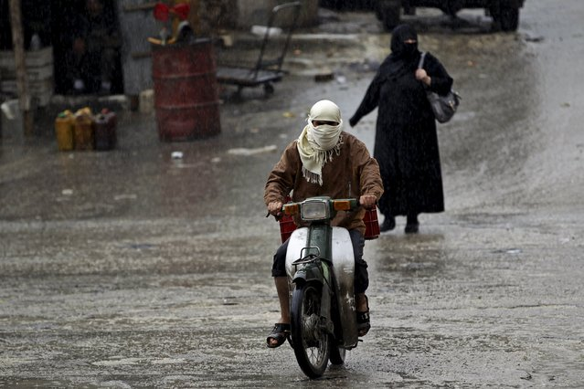 A woman walks past a man riding a scooter in the rain in the rebel-controlled area of Maaret al-Numan town in Idlib province, Syria October 28, 2015. (Photo by Khalil Ashawi/Reuters)