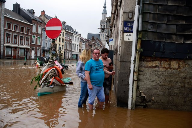 Residents make their way along a flooded street after heavy rains in Ensival, Verviers, Belgium, 15 July 2021. Heavy rains have caused widespread damage and flooding in parts of Belgium. (Photo by Stephanie Lecocq/EPA/EFE/Rex Features/Shutterstock)