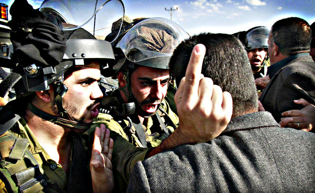 A Palestinian protester argues with Israeli soliders during a demonstration against Israeli settlers who set up tents at the main entrance of Tuqua village, near the West Bank village of Bethlehem, on November 22, 2013. (Photo by Musa Al-Shaer/AFP Photo)