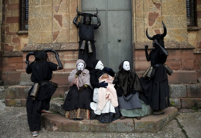 "Revellers, dressed as ""Diablos de Luzon"" (Luzon Devils), and others dressed as ""Mascaritas"" pose during carnival celebrations in the village of Luzon, Spain, February 6, 2016. (Photo by Sergio Perez/Reuters)"