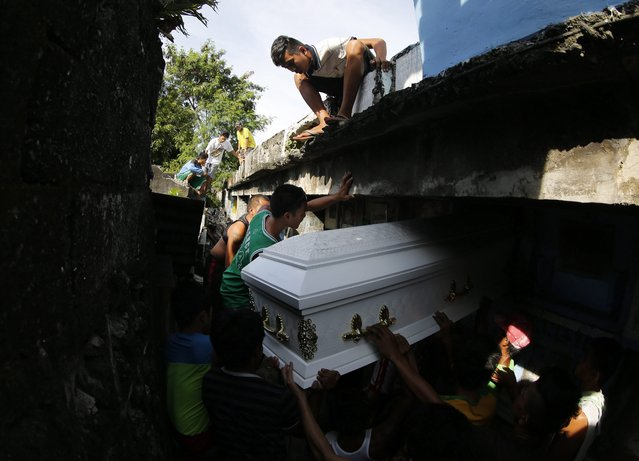A Filipino boy looks on as mourners burry the coffin of a slain alleged drug dealer, who was allegedly killed in a police operation against illegal drugs, during burial rites at a cemetery in Manila, Philippines, 09 October 2016. (Photo by Francis R. Malasig/EPA)