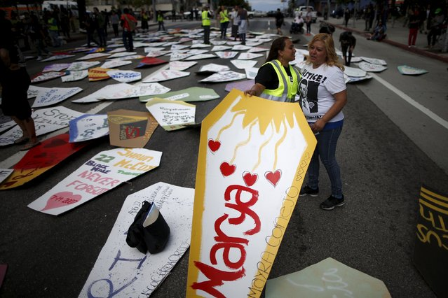 A woman lays a cardboard coffin in the middle of the road during a march to commemorate the more than 617 people march organizers say have been killed by law enforcement in LA County since 2000, in Los Angeles, California April 7, 2015. (Photo by Lucy Nicholson/Reuters)