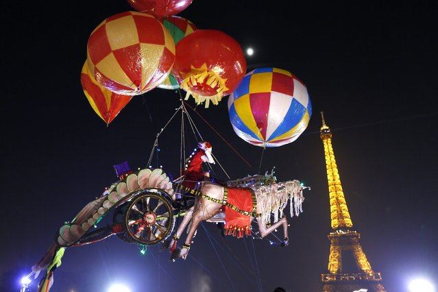 Helium-filled balloons suspend a Santa Claus figure riding a horse-drawn chariot made of balsa wood, created by artist Nasser Volant, near the Eiffel Tower in Paris December 12, 2013. (Photo by Charles Platiau/Reuters)