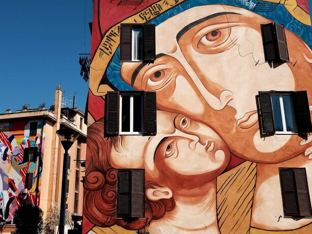 "A picture shows a mural entitled ""Santa Maria di Shangai"" by Italian artist MR Klevra on April 9, 2015 in the Tor Marancia district of Rome. The mural is part of the ""Big City Life Tor Marancia"" project currated by 999Contemporary with the help of the Fondazione Roma and the city of Rome, 20 Street Art artists from 10 countries transformed the housing of the historic Lot 1 of Tor Marancia into a colorful open-air museum dedicated to the street art. (Photo by Alberto Pizzoli/AFP Photo)"