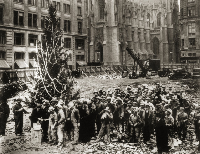 Construction workers line up for pay beside the first Rockefeller Center Christmas tree in New York in 1931.  The Christmas tree went on to become an annual tradition and a New York landmark. St. Patrick's Cathedral is visible in the background on Fifth Avenue. (Photo by AP Photo)