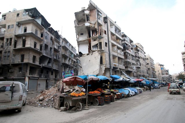 Stalls are seen on a street beside damaged buildings in the rebel held al-Shaar neighborhood of Aleppo, Syria, February 10, 2016. (Photo by Abdalrhman Ismail/Reuters)