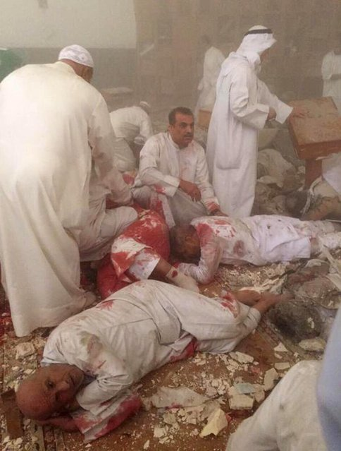 In this June 26, 2015 file photo provided by Kuwaitna news shows injured people in the immediate aftermath of a deadly blast at a Shiite mosque, claimed by  the Islamic State group, in Kuwait City. Twenty five years after the first U.S. Marines swept across the border into Kuwait in the 1991 Gulf War, American forces find themselves battling the extremist Islamic State group, born out of al-Qaida, in the splintered territories of Iraq and Syria. (Photo by Kuwaitna News via AP Photo)