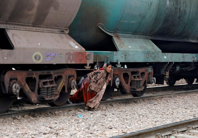 A woman crosses a railway track under an oil tanker train stationed at a railway station in Ghaziabad, on the outskirts of New Delhi, India, February 1, 2019. (Photo by Anushree Fadnavis/Reuters)