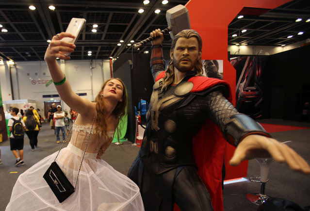A woman takes a selfie next to a model of Thor during the Middle East Film & Comic Con (MEFCC) in Dubai, United Arab Emirates, Saturday, April 11, 2015. (Photo by Kamran Jebreili/AP Photo)
