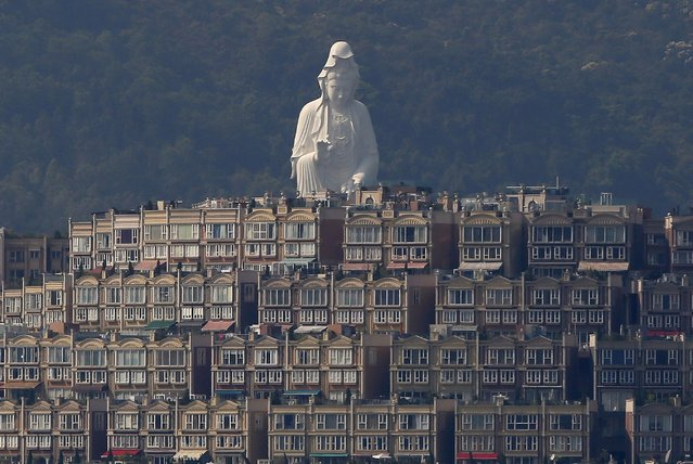 A 76-meter-high (249-feet) bronze-forged white Buddhist Avalokitesvara or Guan Yin statue, part of the Tsz Shan Monastery, stands behind luxurious houses at Taipo district in Hong Kong April 16, 2015. The monastery, officially opened to the public by reservation on April 15, 2015. (Photo by Bobby Yip/Reuters)