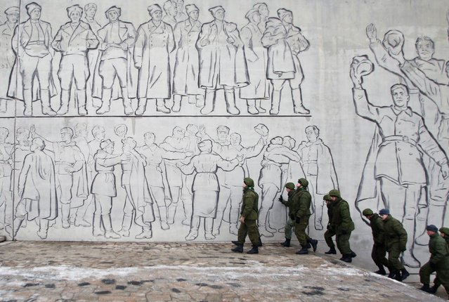 Russian soldiers patrol the Battle of Stalingrad memorial in Volgograd, Russia, Tuesday, December 31, 2013. Russian authorities ordered police to beef up security at train stations and other facilities across the country after a suicide bomber killed 14 people on a bus Monday in the southern city of Volgograd. It was the second deadly attack in two days on the city that lies just 400 miles (650 kilometers) from the site of the 2014 Winter Olympics. (Photo by Denis Tyrin/AP Photo)