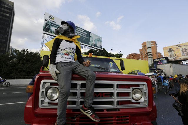 A demonstrator take control of a truck to block a highway after a demonstration demanding the resignation of President Nicolas Maduro, in Caracas, Venezuela, Saturday, February 2, 2019. Momentum is growing for Venezuela's opposition movement led by Guaido, who has called supporters back into the streets for nationwide protests Saturday, escalating pressure on Maduro to step down. (Photo by Fernando Llano/AP Photo)