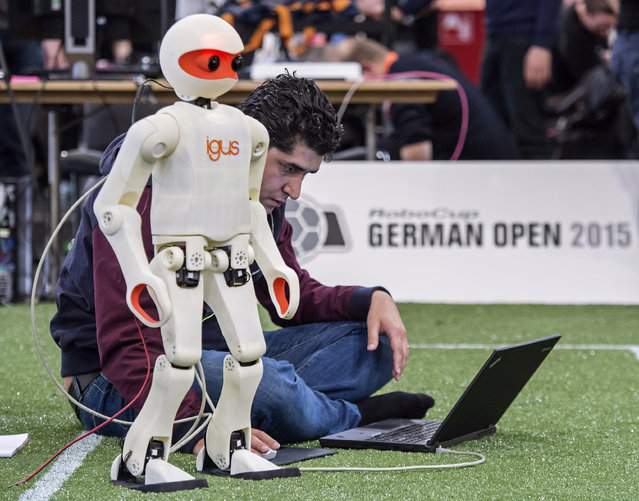Iranian student Hafez Farazi of the German university Bonn codes his robot on the soccer field at the RoboCup German Open 2015 in Magdeburg, Germany, Friday, April 24, 2015. (Photo by Jens Meyer/AP Photo)