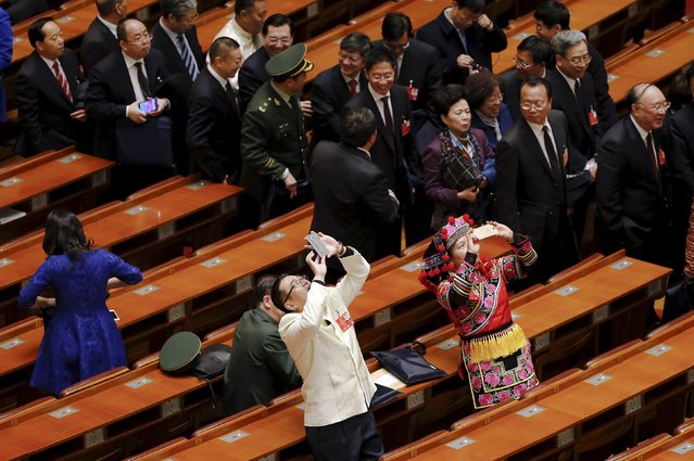 Ethnic minority delegates take pictures as they leave at the end of the opening session of the National People's Congress (NPC) at the Great Hall of the People in Beijing, China, March 5, 2016. (Photo by Kim Kyung-hoon/Reuters)