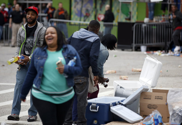 People take items from a business cooler after a march to City Hall for Freddie Gray, Saturday, April 25, 2015 in Baltimore. (Photo by Alex Brandon/AP Photo)