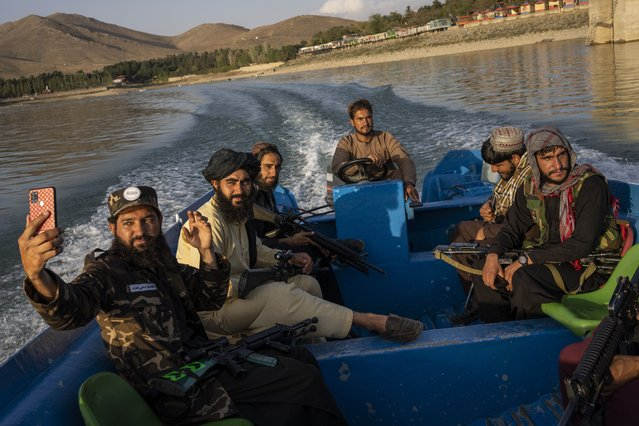 Taliban fighters enjoy a boat ride in the Qargha dam, outskirt of Kabul, Afghanistan, Friday, September 24, 2021. (Photo by Bernat Armangue/AP Photo)