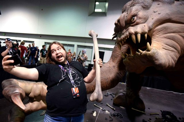 A Star Wars fan takes a selfie with the Roxy the Rancor exhibit at Star Wars Celebration: The Ultimate Fan Experience held at the Anaheim Convention Center on Thursday, April 16, 2015, in Anaheim, Calif. (Photo by Richard Shotwell/Invision/AP Photo)