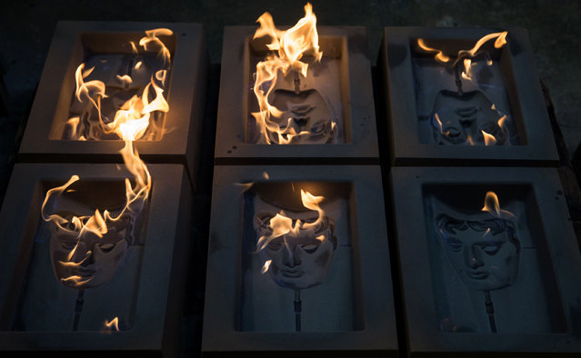 BAFTA (British Academy of Film and Television Arts) mask moulds are set alight to burn off any impurities before casting, during a photocall at the New Pro Foundries, west of London on January 31, 2017. The masks will be presented to winners at BAFTA's awards ceremony in London on February 12, 2017. (Photo by Daniel Leal-Olivas/AFP Photo)