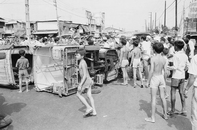 Saigon youngsters mill around overturned three wheeled minibuses during a demonstration by the vehicles drivers protesting various economic issues. The protest was one of two which tock place, March 25, 1975 in the South Vietnamese capital Saigon. (Photo by AP Photo)