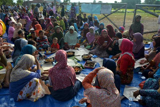Villagers from Banjar Asri and Kedungbanteng sit in front of the Tanggulangin 1 gas well belonging to Indonesian energy company Lapindo Brantas, at the Kedungbanteng village in Sidoarjo, January 12, 2016, in this photo taken by Antara Foto. Indonesian energy company Lapindo Brantas plans to resume drilling for gas near the site of a mud volcano, its CEO said, referring to a disaster that some scientists say it helped to create around 10 years ago. (Photo by Umarul Faruq/Reuters/Antara Foto)
