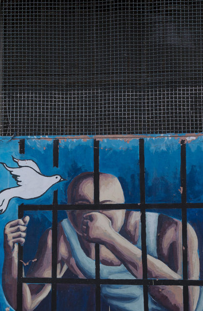This April 14, 2015 photo shows a mural of a prisoner behind bars and a flying dove on the wall inside a courtyard at the now empty Garcia Moreno Prison, during a guided tour for the public in Quito, Ecuador. Psychologist Oscar Ortiz, who worked with the inmates behind these walls, organized local artists to collaborate with the prisoners to adorn the walls with paintings. (Photo by Dolores Ochoa/AP Photo)