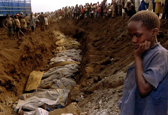 A Rwandan refugee girl stares at a mass grave where dozens of bodies were laid to rest, July 20, 1994. (Photo by Corinne Dufka/Reuters)