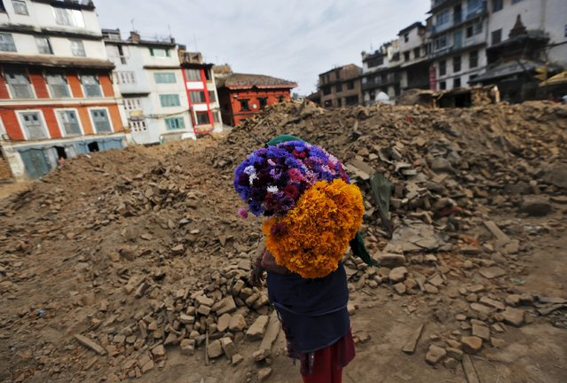 A woman carries flowers as she walks past a destroyed temple at Bashantapur Durbar Square, after the earthquake in Kathmandu, Nepal May 5, 2015. (Photo by Adnan Abidi/Reuters)