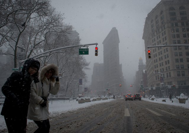 People walk past the Flatiron Building during a winter storm, February 9, 2017 in New York. (Photo by Bryan R. Smith/AFP Photo)