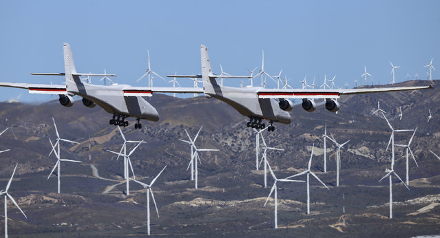 Stratolaunch, a giant six-engine aircraft with the world's longest wingspan , makes its historic first flight from the Mojave Air and Space Port in Mojave, Calif., Saturday, April 13, 2019. Founded by the late billionaire Paul G. Allen, Stratolaunch is vying to be a contender in the market for air-launching small satellites. (Photo by Matt Hartman/AP Photo)