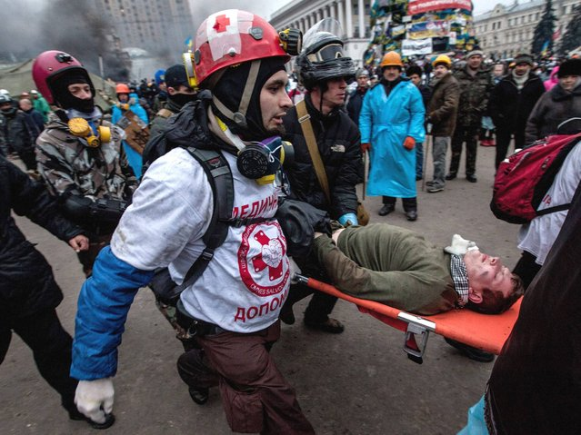 Anti government demonstrators carry a wounded comrade during clashes with riot police on the Independence square in Kiev, on February 20, 2014. (Photo by Yevgeny Maloletka/EPA)