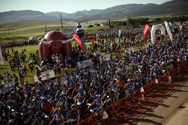 Mountain bikers and runners (L) wait for the start of the XVIII 101km international competition in Ronda, southern Spain, May 9, 2015. (Photo by Jon Nazca/Reuters)