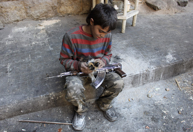 """Mohammad, a 13-year-old fighter from the """"Free Syrian Army"""", plays with a cat in Aleppo's Bustan al-Basha district, Syria October 28, 2013. Mohammad joined the Free Syrian Army after his father died during clashes with the Syrian regime. The gun he is using was his father's. (Photo by Molhem Barakat/Reuters)"""