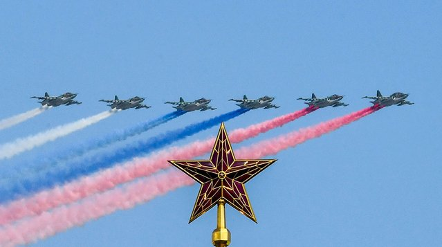 Russian SU-25 assault aircrafts release smoke in the colours of the Russian flag while flying over Moscow's Kremlin Borovitskaya tower during a rehearsal for the Victory Day military parade in Moscow on May 7, 2019. (Photo by Yuri Kadobnov/AFP Photo)