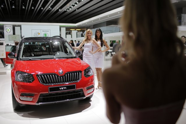 Models take pictures of themselves in front of the new Skoda Yeti during the media day of the 84th Geneva International Motor Show, Switzerland, Tuesday, March 4, 2014. (Photo by Laurent Cipriani/AP Photo)