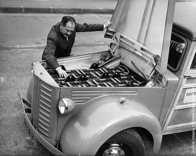 1948: A man examining his electric car