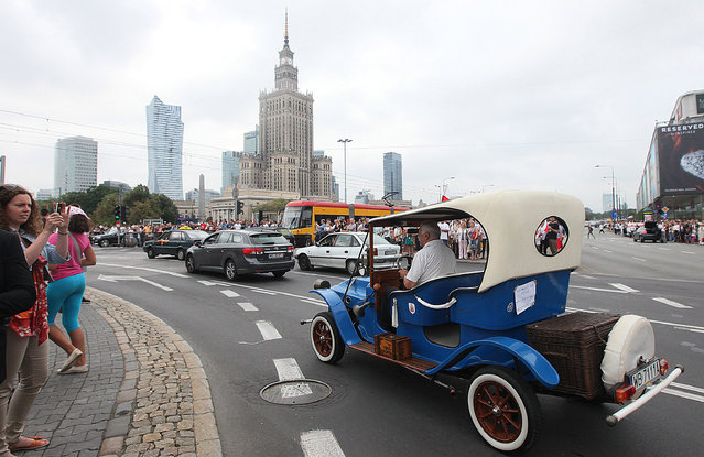 In this Friday, May 8, 2015 photo, cars drive past the communist-era Palace of Culture in Warsaw, Poland. The Warsaw Experience tour offered by the Charm of PRL museum gives visitors a peek at life under Poland's bygone communist system with a visit to a tiny apartment, a taste of cherry vodka and a ride in a militia van. (Photo by Czarek Sokolowski/AP Photo)