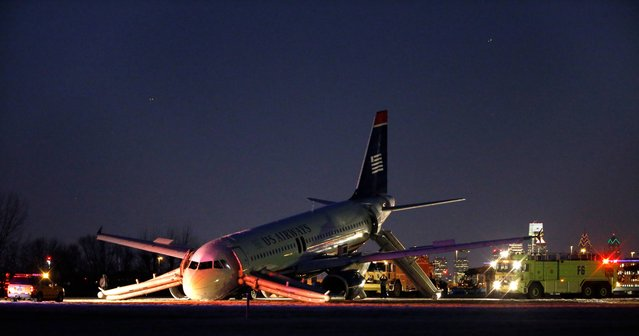 A damaged US Airways jet lies at the end of a runway at the Philadelphia International Airport, Thursday, March 13, 2014, in Philadelphia. Airline officials said the flight was heading to Fort Lauderdale, Fla., when the pilot was forced to abort takeoff around 6:30 p.m., after the front landing gear failed. An airport spokeswoman said no injuries have been reported. (Photo by Matt Slocum/AP Photo)