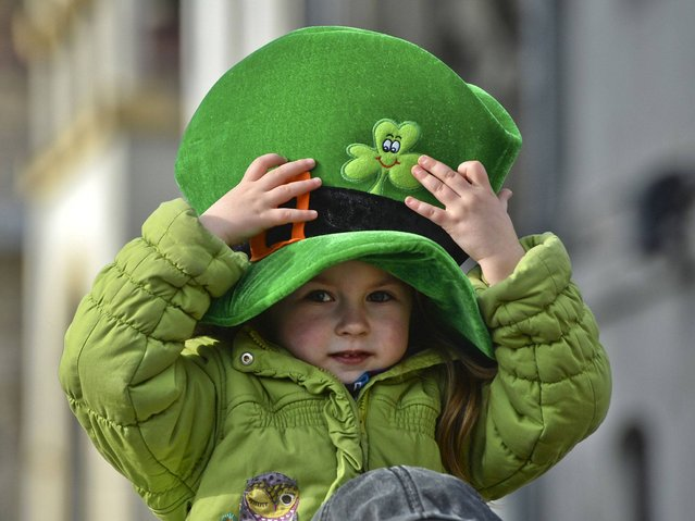 A child wearing a green hat with a shamrock takes part in a parade celebrating St Patrick's Day, in Bucharest, Romania. (Photo by Andreea Alexandru/AP Photo/Mediafax)