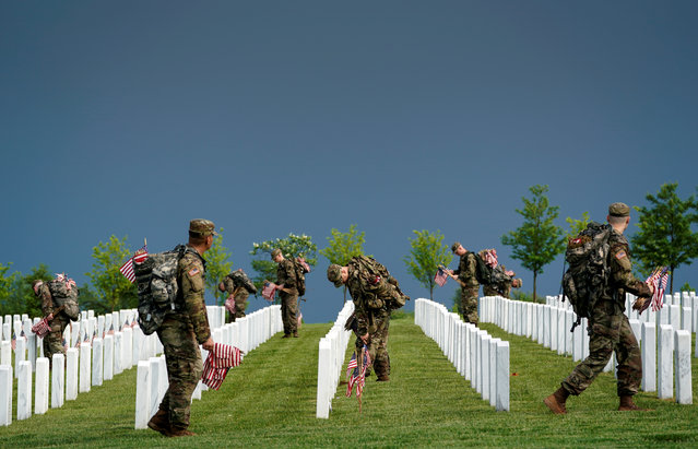 """Old Guard soldiers take part in """"Flags-In"""", an annual event where a small American flag is placed in front of more than 240,000 headstones of U.S. service members buried at Arlington National Cemetery in Arlington, Virginia, U.S., May 23, 2019. (Photo by Kevin Lamarque/Reuters)"""