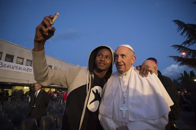 Pope Francis poses for a selfie during his visit at the Castelnuovo di Porto refugees center, some 30km (18, 6 miles) from Rome, Thursday, March 24, 2016. The pontiff washed and kissed the feet of Muslim, Orthodox, Hindu and Catholic refugees Thursday, declaring them children of the same God, in a gesture of welcome and brotherhood at a time when anti-Muslim and anti-immigrant sentiment has spiked following the Brussels attacks. (Photo by L'Osservatore Romano/Pool Photo via AP Photo)