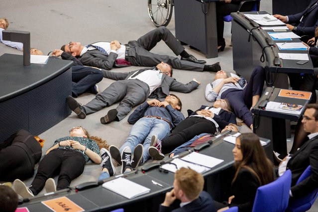 """Participants of a protest action for climate justice by Fridays For Future lie on the floor in the plenary hall of the Bundestag in Berlin, Germany, Tuesday, June 4, 2019. In the simulation game """"Youth and Parliament"""", young people slip into the role of members of the Bundestag. (Photo by Christoph Soeder/dpa via AP Photo)"""